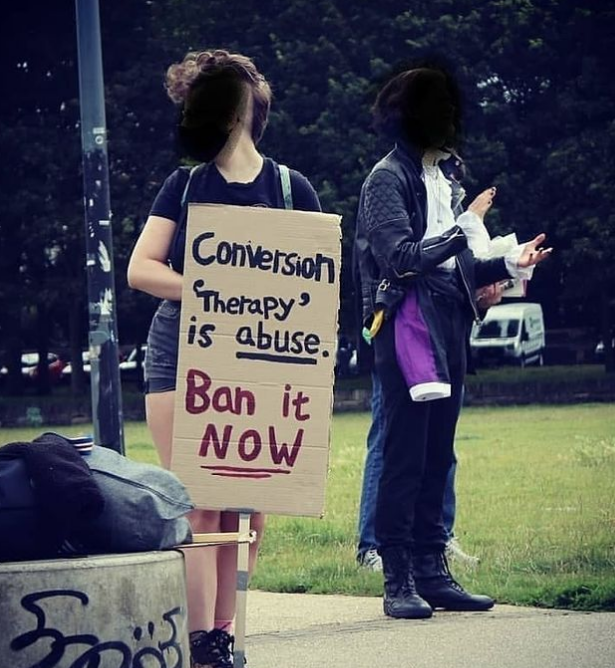 """A protestor holding a sign that reads 'Conversion """"therapy"""" is abuse. Ban it NOW.'"""